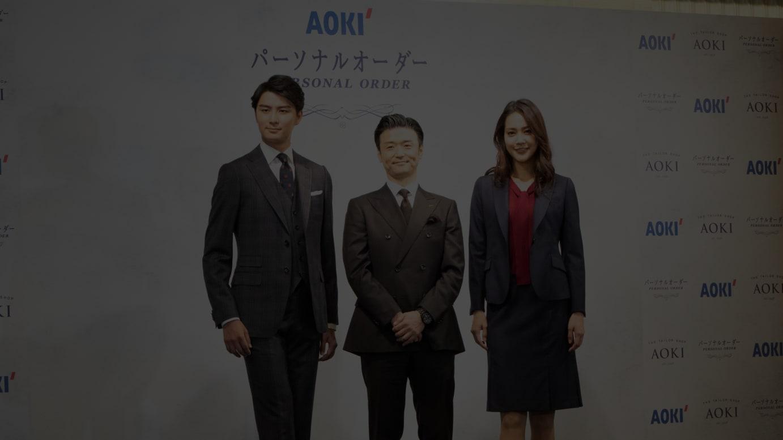 オーダースーツを着用したモデルとAOKIホールディングスの青木彰宏 代表取締役社長