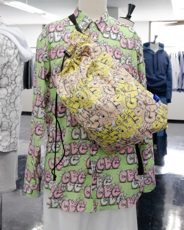 カウズによる「CDG」のグラフィックをあしらったシャツとバッグ