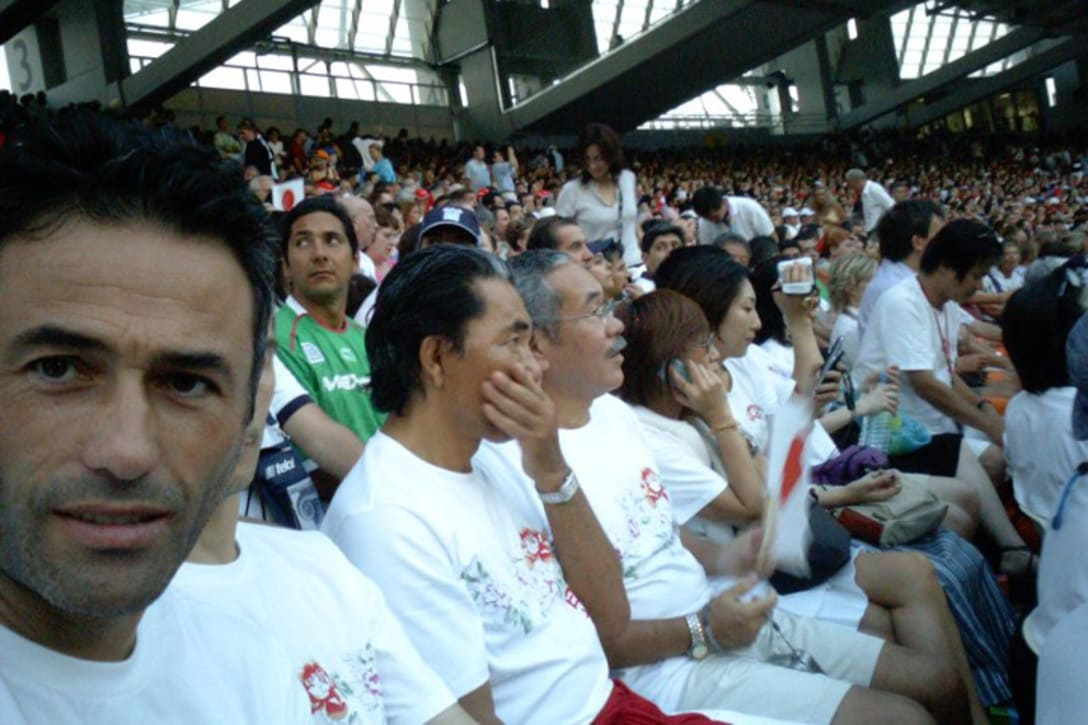 観客席で競技を見つめる高田賢三(中央)は真剣な表情(筆者提供)